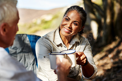 Buy stock photo Shot of a cheerful senior woman sharing a toast with her husband while exploring out in the mountains
