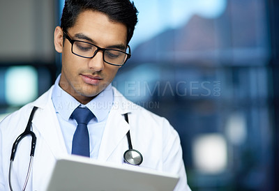 Buy stock photo Shot of a young doctor using a digital tablet in a hospital