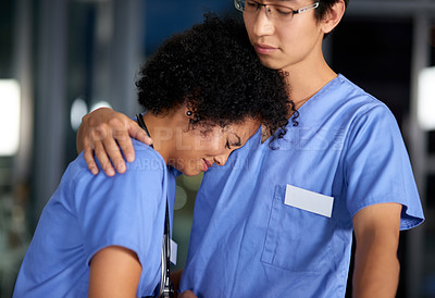 Buy stock photo Shot of a medical practitioner consoling an unhappy colleague in a hospital