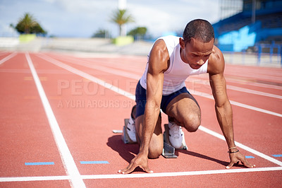 Buy stock photo Full length shot of a male sprinter getting ready to run on a track
