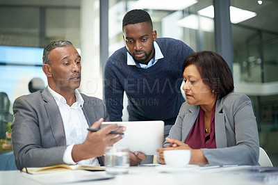 Buy stock photo Shot of corporate businesspeople using a digital tablet together inside a modern office