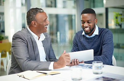Buy stock photo Shot of two corporate businessmen using a digital tablet together in a modern office