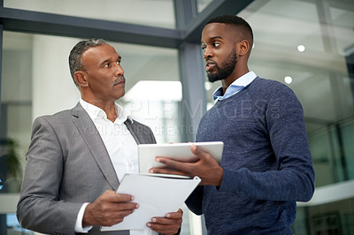 Buy stock photo Shot of two corporate businessmen using a digital tablet and going over some paperwork together at work