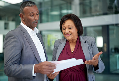 Buy stock photo Shot of two mature businesspeople going over some paperwork together inside an office