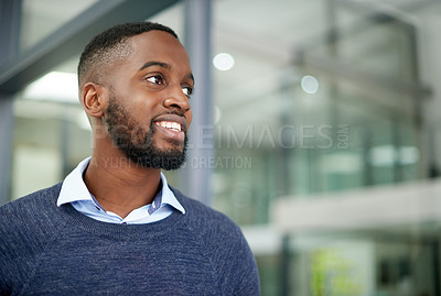 Buy stock photo Shot of a handsome young businessman looking thoughtful while standing inside his office at work