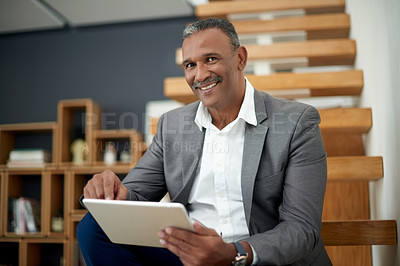 Buy stock photo Portrait of a handsome mature businessman using a digital tablet in his office