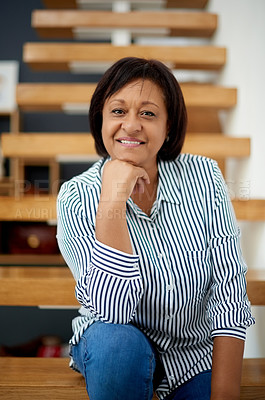 Buy stock photo Portrait of an attractive mature woman sitting on a staircase at home