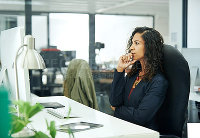 Buy stock photo Cropped shot of an attractive young businesswoman sitting and looking at her computer screen while in her office