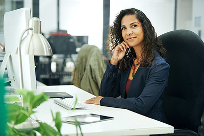 Buy stock photo Cropped portrait of an attractive young businesswoman sitting with her hand on her chin while in the office