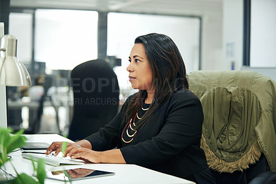 Buy stock photo Cropped shot of an attractive mature businesswoman sitting and using a computer while in the office during the day