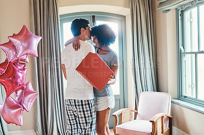 Buy stock photo Shot of a young man surprising his girlfriend with gifts and balloons in their bedroom at home