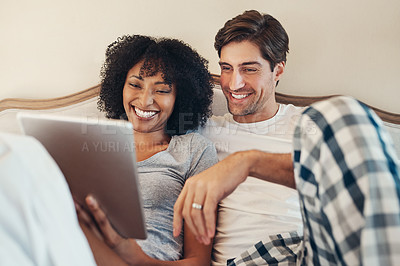 Buy stock photo Shot of an affectionate young couple using a digital tablet while spending time together in bed at home
