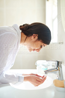Buy stock photo Cropped shot of a young woman washing her face in the bathroom basin