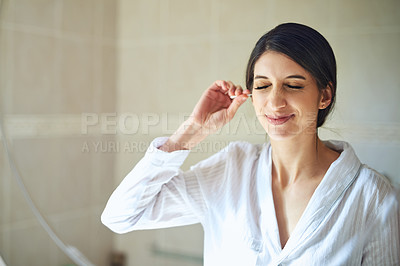 Buy stock photo Cropped shot of an attractive young woman cleaning her ears with a earbud