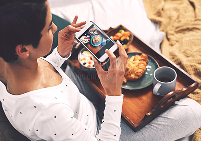 Buy stock photo Cropped shot of an attractive young woman using her cellphone to take a picture of her breakfast tray while at home