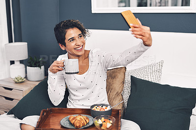 Buy stock photo Full length shot of an attractive young woman taking a selfie while posing with her breakfast tray in bed