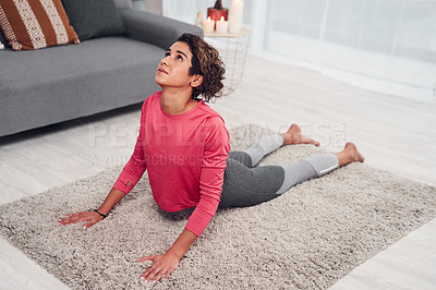Buy stock photo Full length shot of an attractive young woman doing yoga in her living and holding an upward facing dog position