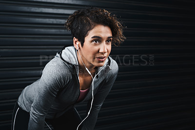 Buy stock photo Cropped shot of an attractive young woman wearing earphones and taking a break against a black background after exercising