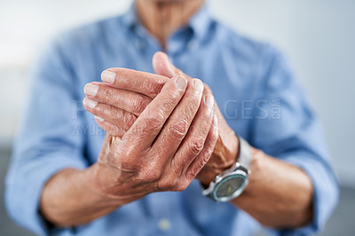 Buy stock photo Shot of an unrecognizable senior man holding his hand in pain