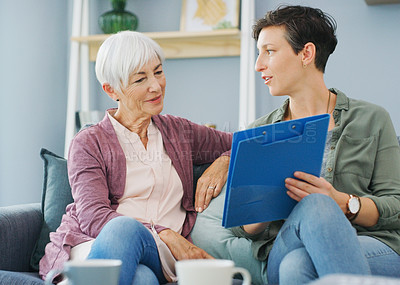Buy stock photo Cropped shot of an attractive young healthcare professional sitting with her senior patient and discussing her medical results