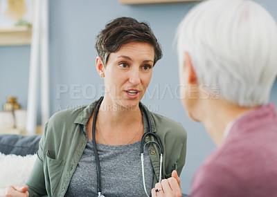 Buy stock photo Cropped shot of an attractive young healthcare professional sitting and talking to her senior patient while in the living room