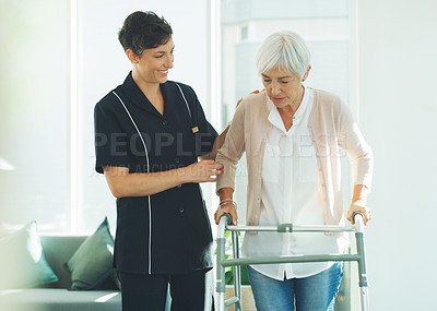 Buy stock photo Cropped shot of an attractive young healthcare professional helping her senior patient walk with a walker in a nursing home