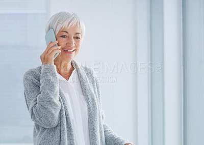 Buy stock photo Cropped shot of a happy senior woman standing with her walker while talking on her cellphone in the nursing home