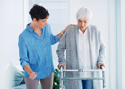 Buy stock photo Cropped shot of an attractive young woman helping her senior mother walk with her walker in a nursing home