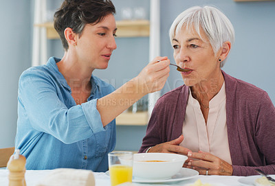 Buy stock photo Cropped shot of an attractive young woman helping and feeding her senior mother while they have breakfast together at home