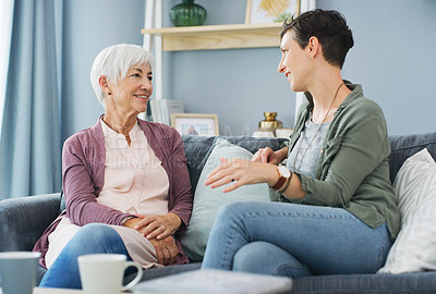 Buy stock photo Cropped shot of an attractive young woman sitting on the sofa and talking with her happy senior mother at home