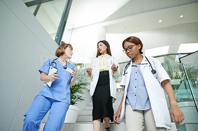 Buy stock photo Shot of a team of young doctors having a discussion on the steps of a modern hospital