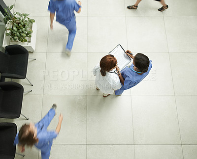 Buy stock photo High angle shot of two young doctors having a discussion in a modern hospital