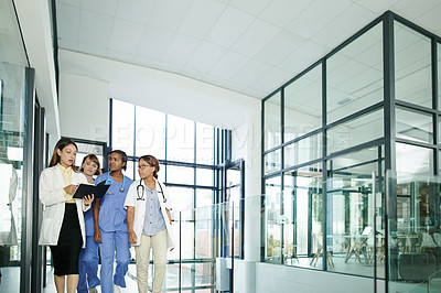 Buy stock photo Shot of a team of young doctors having a discussion wile walking through a modern hospital