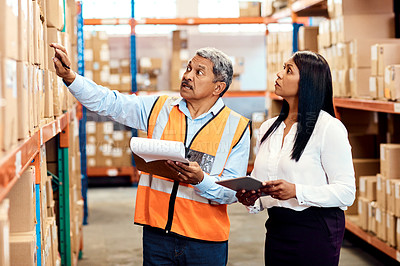 Buy stock photo Shot of a mature man and woman working together in a warehouse