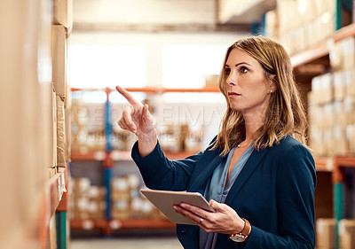Buy stock photo Shot of a young factory manager using a digital tablet in a warehouse