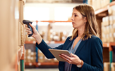 Buy stock photo Shot of a young factory manager using a barcode reader and digital tablet in a warehouse
