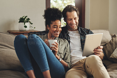 Buy stock photo Shot of a happy young couple using a digital tablet together while relaxing on a couch at home