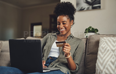 Buy stock photo Shot of a beautiful young woman using her credit card and laptop while relaxing on a sofa at home