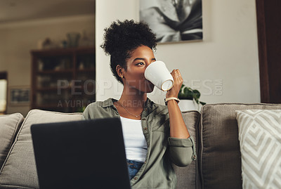 Buy stock photo Shot of a beautiful young woman drinking coffee and while working on her laptop at home