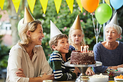 Buy stock photo Shot of a happy family celebrating a birthday at home in the garden