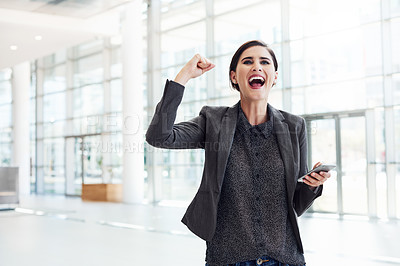 Buy stock photo Cropped shot of an attractive young businesswoman cheering in excitement while holding her cellphone in the office during the day