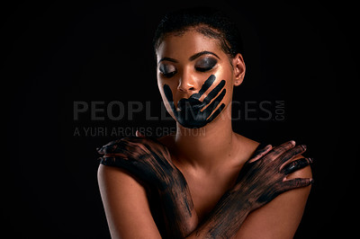 Buy stock photo Studio shot of a young woman with a hand painted on her mouth posing against a black background