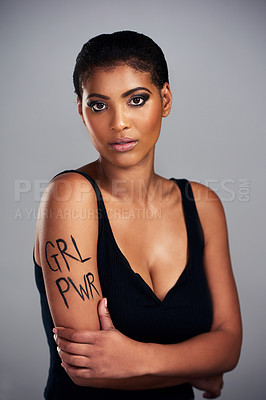 "Buy stock photo Studio shot of a young woman with ""grl pwr"" painted on her arm posing against a grey background"