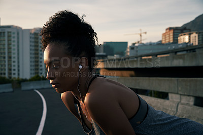 Buy stock photo Cropped shot of an attractive young woman wearing earphones and crouching while outside in the city after her morning run