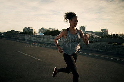 Buy stock photo Cropped shot of an attractive young woman running alone while outdoors in the city during sunrise