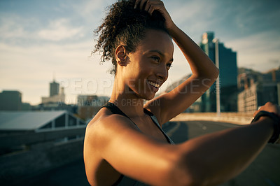 Buy stock photo Cropped shot of an attractive young woman wearing earphones and looking at her watch before running in the morning