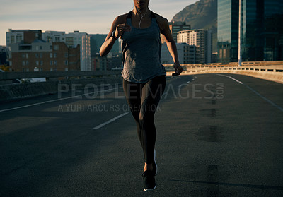 Buy stock photo Cropped shot of an unrecognizable young woman running in the city during the morning