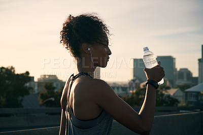 Buy stock photo Cropped shot of an attractive young woman wearing earphones and drinking water after her morning run in the city