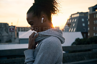 Buy stock photo Cropped shot of an attractive young woman wearing earphones before going on a morning run in the city