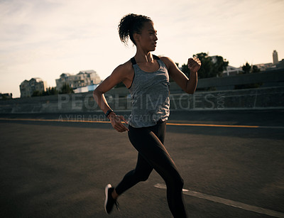 Buy stock photo Cropped shot of an attractive young woman running in the morning while outdoors in the city